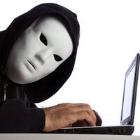 Man in a mask hacking a laptop